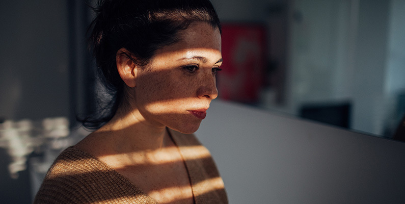 Woman sitting in dark room