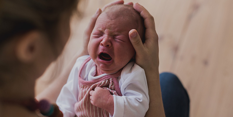 Crying baby held by mother