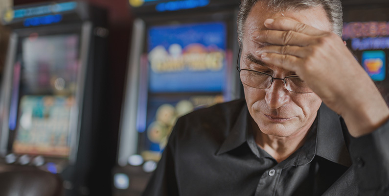 Man holding head in hands with slot machines in the background