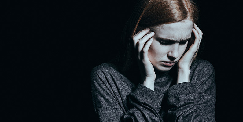 Young woman sitting in dark room holding her head in her hands