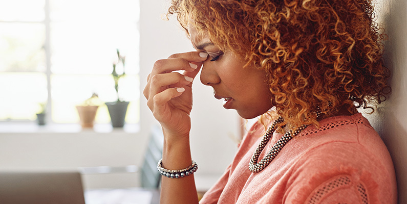 Woman suffering fatigue holds the bridge of her nose with eyes closed, breathing deeply.